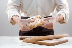 Hombre del panadero que sostiene la barra de pan orgánica rústica en manos Foto de archivo