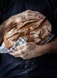 Hombre del panadero que sostiene la barra de pan rústica en manos Foto de archivo