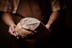 Hombre del panadero que sostiene un pan redondo Imagenes de archivo