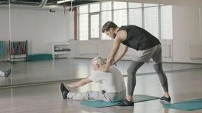 Hombre del pensionista que hace estirando ejercicio con el instructor de la aptitud en gimnasio junto almacen de metraje de vídeo