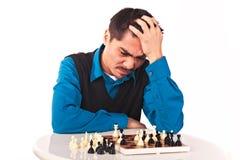 Hombre que juega a ajedrez en el fondo blanco Foto de archivo