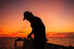 hombre del pescador en puesta del sol Imágenes de archivo libres de regalías