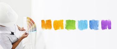 Hombre del pintor con las muestras en su mano, colores bien escogidos del color Fotos de archivo libres de regalías
