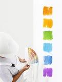 Hombre del pintor con muestras del color en su mano, opción de los colores c Foto de archivo