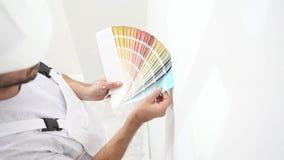Hombre del pintor en el color bien escogido con las muestras de las muestras, concepto de la pintura de pared, espacio blanco del almacen de video