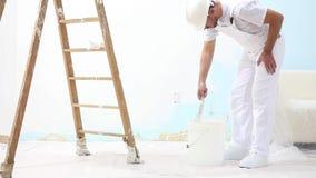 Hombre del pintor en el trabajo con el cepillo, concepto de la pintura de pared, fondo blanco almacen de metraje de vídeo