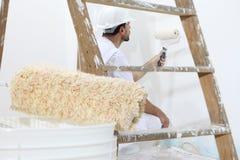 Hombre del pintor en el trabajo con el rodillo de pintura, concepto de la pintura de pared Fotos de archivo