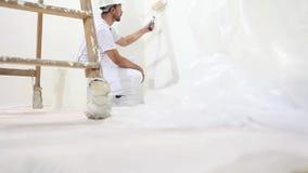 Hombre del pintor en el trabajo, con la pared de la pintura del rodillo, y escalera de madera almacen de metraje de vídeo