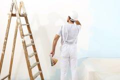 Hombre del pintor en el trabajo con las muestras de las muestras del color, pintura de pared Imágenes de archivo libres de regalías