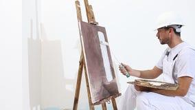 Hombre del pintor en el trabajo con el rodillo de pintura, el caballete, la lona y la paleta, concepto de la pintura de pared, fo almacen de metraje de vídeo