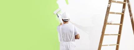 Hombre del pintor en el trabajo con un rodillo de pintura, cuesta del verde de la pintura de pared fotos de archivo libres de regalías