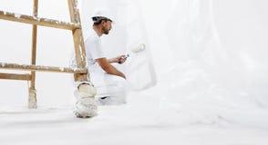 Hombre del pintor en el trabajo con un rodillo de pintura en la pared Imagenes de archivo