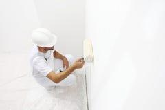Hombre del pintor en el trabajo con un rodillo de pintura, pintura de pared Imagen de archivo libre de regalías