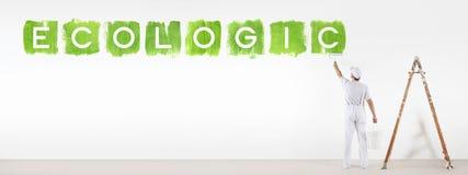 Hombre del pintor que pinta el texto ecológico del color verde aislado en la pared imágenes de archivo libres de regalías