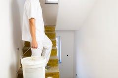 Hombre del pintor que trabaja en las paredes blancas de una pintura de casa imagenes de archivo