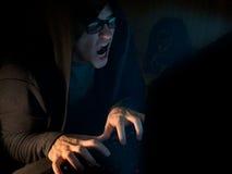 Hombre del pirata informático de ordenador que roba la información con el ordenador portátil imagenes de archivo