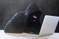 Hombre del pirata informático en capilla negra y máscara con el ordenador portátil del ordenador que corta el sistema en concepto Fotos de archivo libres de regalías
