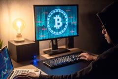 Hombre del pirata informático que usa el ordenador para la moneda digital que lava plancha foto de archivo libre de regalías