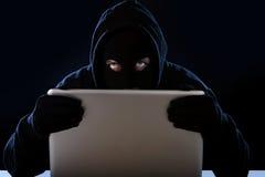 Hombre del pirata informático en capilla negra y máscara con el ordenador portátil del ordenador que corta el sistema en concepto Imagen de archivo