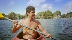 Hombre del primer con el kajak desnudo de los remos del torso al revés contra las islas almacen de video