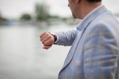 Hombre del primer con el reloj en una mano Hombre de negocios que comprueba tiempo en un fondo borroso de la ciudad Concepto del  fotografía de archivo