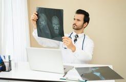 Hombre del radiólogo que comprueba el resultado de la radiografía, la atención sanitaria, médicos y imagen de archivo