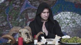 Hombre del retrato en la ropa negra con la capilla en la cabeza que se sienta en la pequeña tabla delante de las velas, uvas, y almacen de video