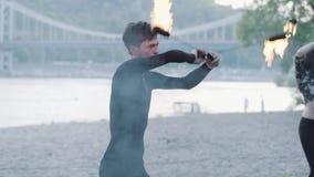 Hombre del retrato que realiza una demostración con la situación de la fan del fuego en riverbank delante de árboles Baile expert metrajes