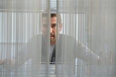 Hombre del retrato a través de la malla metálica imagen de archivo libre de regalías