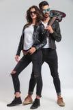 Hombre del rock-and-roll con la guitarra en mujer de abarcamiento del hombro Imágenes de archivo libres de regalías
