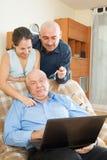 Hombre del Senor halping con el ordenador portátil Fotos de archivo