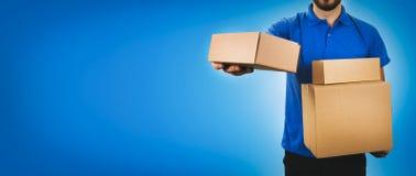 hombre del servicio de entrega que sostiene las cajas de cartón en fondo azul fotografía de archivo