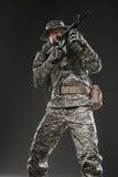 Hombre del soldado de las fuerzas especiales con la ametralladora en un fondo oscuro Imagen de archivo libre de regalías