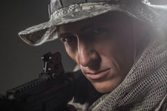 Hombre del soldado de las fuerzas especiales con la ametralladora en un fondo oscuro Foto de archivo libre de regalías