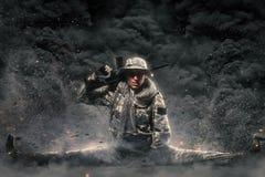 Hombre del soldado de las fuerzas especiales con la ametralladora en un fondo oscuro Imágenes de archivo libres de regalías