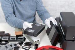 Hombre del técnico con el casete de VHS para la numeración foto de archivo libre de regalías