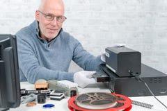 Hombre del técnico con el casete de VHS para la numeración fotos de archivo libres de regalías