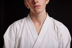 Hombre del Taekwondo del primer en un fondo negro Combatiente adolescente en un uniforme blanco Concepto de la competición Fotos de archivo