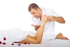 Hombre del terapeuta que da masajes a la pierna de la mujer Imagenes de archivo