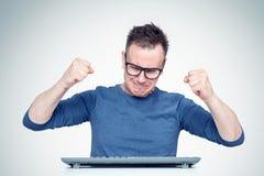 Hombre del trastorno en vidrios detrás de un teclado delante de un ordenador, agitando emocionalmente sus puños en el teclado Con fotografía de archivo libre de regalías