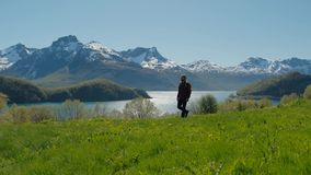 Hombre del viaje que camina en una colina de la hierba verde con el paisaje imponente Noruega de la montaña almacen de metraje de vídeo
