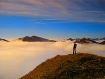 Hombre del viajero con la mochila que disfruta de una visión a un valey en una montaña Fotos de archivo libres de regalías