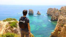 Hombre del viajero con la mochila que goza y que se relaja delante de la visión imponente en Portugal meridional Opinión trasera  imagen de archivo