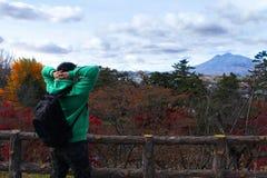 Hombre del viajero con la mochila que mira paisaje de las montañas fotografía de archivo libre de regalías