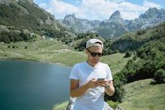 Hombre del viajero en un casquillo y las gafas de sol que se colocan usando el smartphone a imagen de archivo libre de regalías