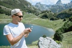 Hombre del viajero en un casquillo y las gafas de sol que se colocan usando el smartphone a imágenes de archivo libres de regalías