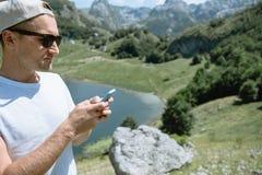 Hombre del viajero en un casquillo y las gafas de sol que se colocan usando el smartphone a fotos de archivo