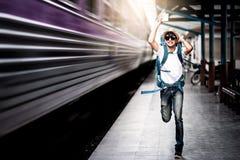 Hombre del viajero que corre después de un tren móvil imagen de archivo