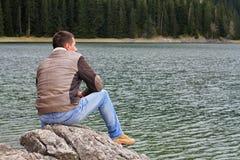 Hombre del viajero que disfruta de la opinión del lago de la montaña Hombre que mira el horizonte, concepto de la soledad Foto de archivo