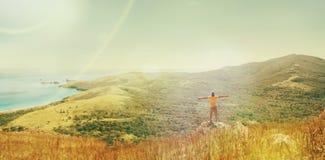 Hombre del viajero que se coloca en el pico de la montaña cerca del mar Imagen de archivo